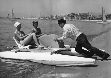 Eddie Constantine aide deux jeunes femmes à mettre leur pédalo à l'eau, 1955